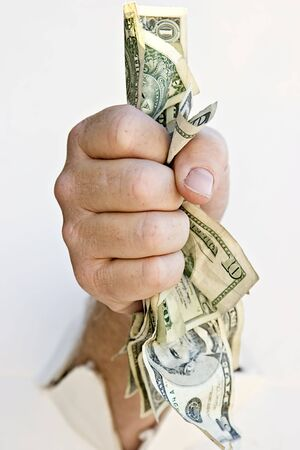 Fist clenching money breaking through a wall photo