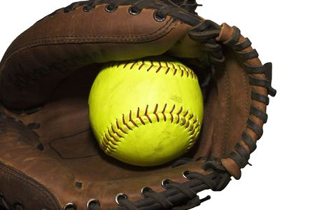 Yellow softball in a catchers glove isolated on a white background Stock Photo