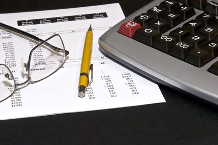 Reading glasses on top of a financial statement with a yellow pencil and a calculator Archivio Fotografico
