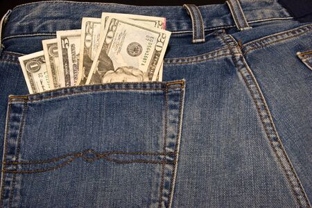 Pair of blue jeans with cash in the back pocket Stock Photo