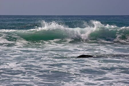 rough: Ocean wave cresting at a beach in Dana Point, California
