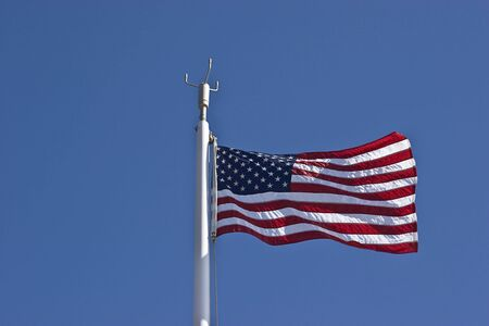 American flag waving in the wind against a blue sky