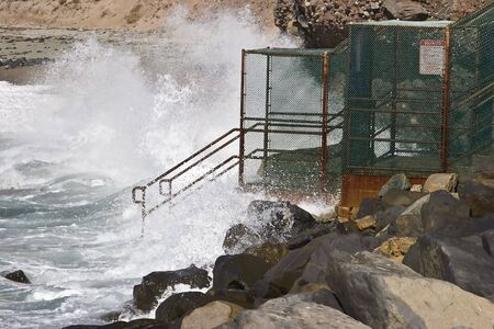 Wave crashing against a beach entrance in Dana Point, California