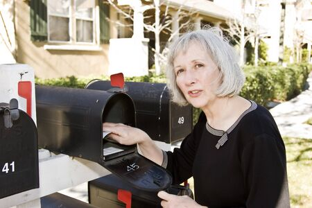 An attractive woman talking to her neighbor while she checks her mailbox Stock Photo