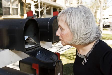 An attractive mature woman is concerned with what she sees inside her mailbox photo