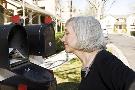An attractive mature woman is pleased with what she sees in her mailbox Stock Photo