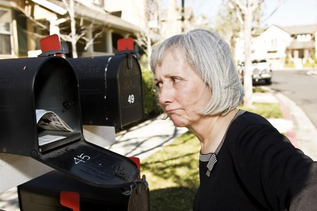An attractive mature woman is perplexed at what is in her mailbox