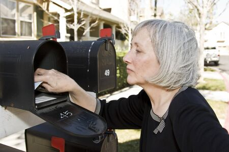 An attractive mature woman is removing mail from her mailbox