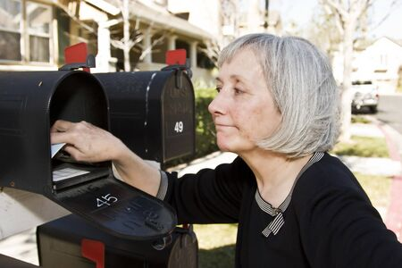 An attractive mature woman checking her mailbox photo