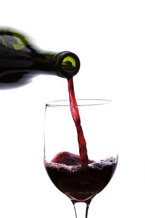 Pouring red wine into a glass isolated on a white background Stock Photo