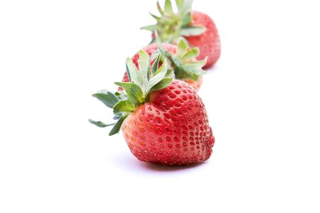 Row of strawberries with selective focus on the first piece of fruit