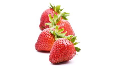 Line of strawberries with selective focus on first piece of fruit isolated on white