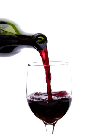 Pouring a glass of red wine into a glass on a white background Stock Photo