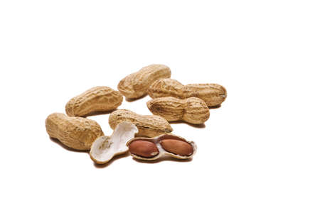 Loose peanuts on a table isolated on white background with drop shadows