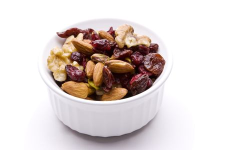Bowl of dried fruit and nuts isolated on white with a drop shadow