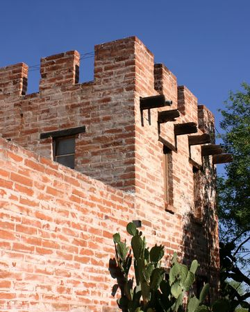 joists: Brick building in historic art colony town of Tubac in Arizona showing simulated ramparts on the roof line plus windows jutting roof joists cactus and tree Stock Photo