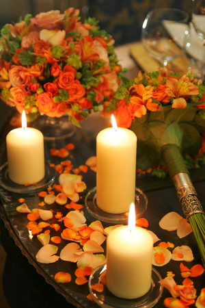 A close up portrait of three burning candles on a table, with some rose and flower petals scattered all around. Stock Photo