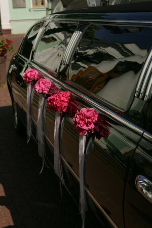 A general view of the side of a wedding car black limousine, seen here decorated with four bouquets of red flowers. photo