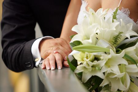 half body: A half body portrait of a newly married couple seen here holding hands. The bride is wearing a traditional white wedding dress and holding a bouquet of flowers.