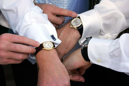 synchronizing: A groom and his two groomsmen synchronizing their watches before a wedding