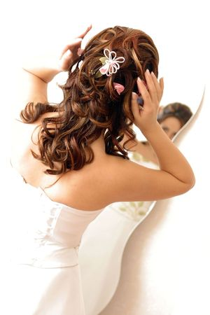 A woman in a white dress looking at her hair in a mirror