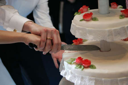 A bride and groom cutting hte wedding cake at their wedding photo
