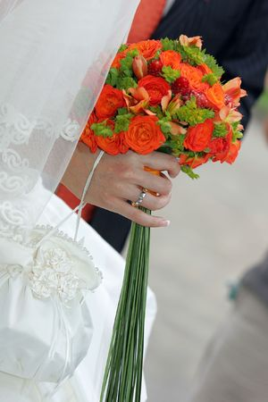 seem: A bride in white seem here holding some red flowers