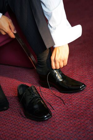 black carpet: Businessman putting on his smart shoes to go to work Stock Photo