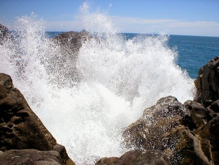 crashing: Waves crashing on a rocky shoreline and throwing up some spray