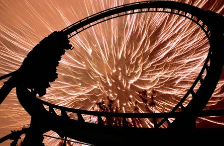 exhilaration: Some people on a rollercoaster at night illuminated in silhouette