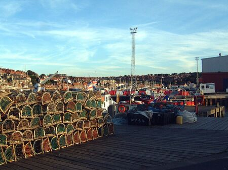 A general view of some lobster pots lined up on the quayside in Whitby Harbour in North Yorkshire, in England in the U.K.  photo