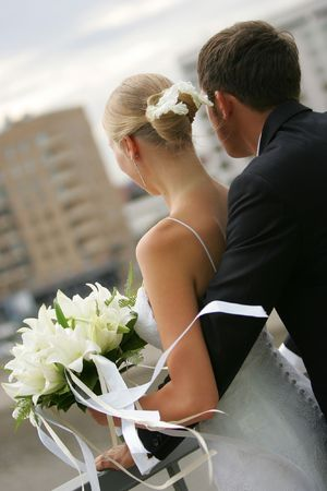 Newly married couple looking out of their hotel bedroom window Stock Photo - 1806205