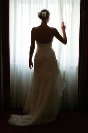 A full body portrait of a bride in a traditional white wedding dress at a wedding, pictured here stood in silhouette standing at her hotel bedroom window after the ceremony. Stock Photo - 1806188