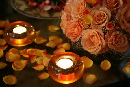 Burning candles surrounded by flower petals and a bouquet photo