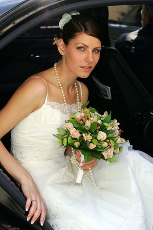 A bride getting out of her wedding car holding a bouqut of flowers Stock Photo