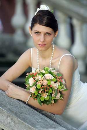 Portrait of a bride in a white wedding dress holding a bouquet Stock Photo - 1858542