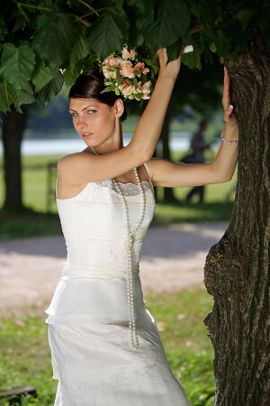 under a tree: Portrait of a bride in white posing under a tree with a bouquet