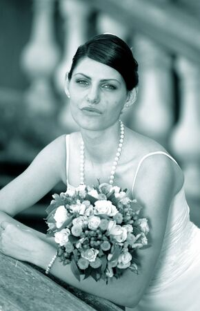 wistful: Portrait of a bride in white holding a bouquet and looking wistful