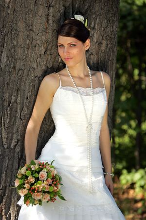 Portrait of a bride in a qhite wedding dress standing by a tree with a bouquet Stock Photo - 1858563