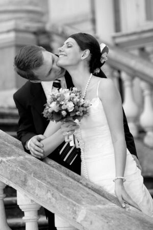 Newly married kissing each oher on some steps