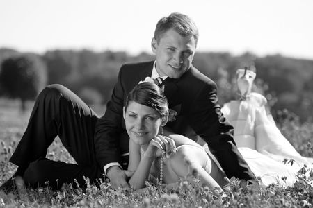 Newly married couple smling in a field with happiness. photo