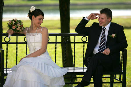 A portrait of a newly married man and woman sat on a bench