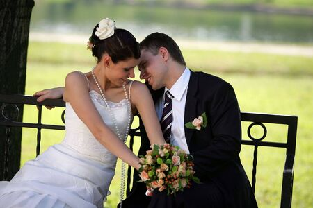 A portrait of a newly married man and woman kissing on a bench.
