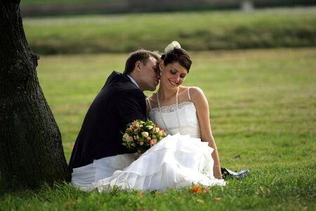 A portrait of a newly married man and woman kissing under a tree photo