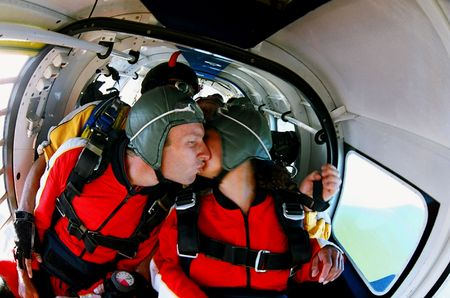 Two people pictured kissing each other before they jump from an aeroplane in a skydive