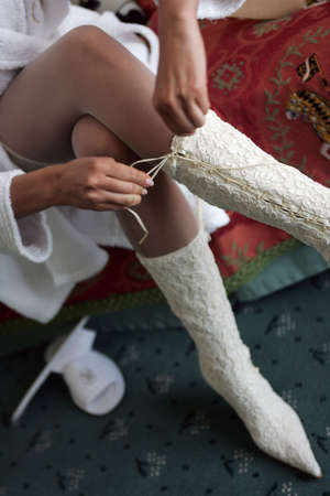 Bride in a traditional white wedding dress tying her boot laces Stock Photo - 2084798