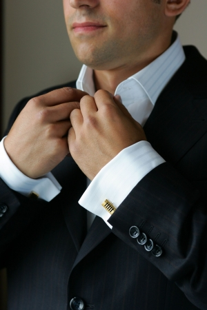 cuff link: A half body portrait of a businessman seen here putting on his tie before he goes to work.