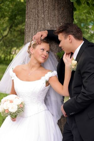 A portrait of a newly married man and woman being romantic in a park Stock Photo - 2123870