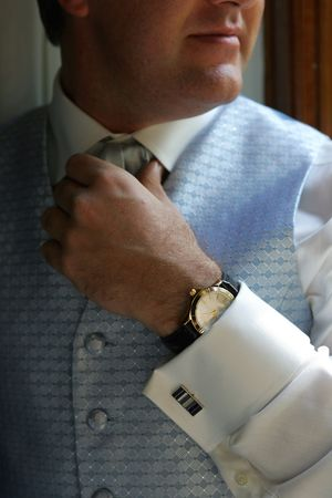 A groom in a waistcoat adjusting his tie before his wedding Stock Photo - 2123868