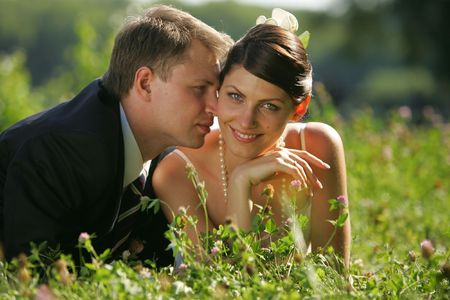A portrait of a newly married man and woman embracing in a field